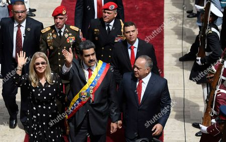 Venezuela's President Nicolas Maduro, center, first lady Cilia Flores, left, and Constituent Assembly President Diosdado Cabello arrive to the grounds of the National Assembly where Maduro will give his annual address to the nation in the Constituent Assembly in Caracas, Venezuela