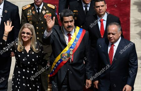 Venezuela's President Nicolas Maduro, center, first lady Cilia Flores, left, and Constituent Assembly President Diosdado Cabello arrive to the grounds of the National Assembly where Maduro will give his annual address to the nation inside the Constituent Assembly in Caracas, Venezuela