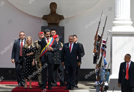 Below the bust of independence hero Simon Bolivar, Venezuelan President Nicolas Maduro, center, first lady Cilia Flores, left, and Constituent Assembly President Diosdado Cabello arrive to the grounds of the National Assembly where Maduro will give his annual address to the nation inside the Constituent Assembly in Caracas, Venezuela