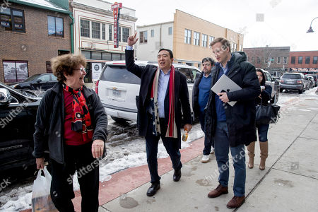 Democratic presidential candidate Andrew Yang jokes with a woman on the street as he arrives at a campaign stop at the Octagon Center For the Arts, in Aimes, Iowa