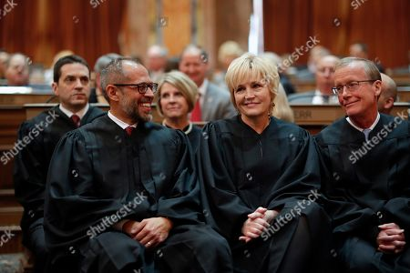 Stock Photo of Iowa Supreme Court Justices Christopher McDonald, left, Susan Christensen, center, and Edward Mansfield, right, share a laugh before Iowa Gov. Kim Reynolds delivers her Condition of the State address before a joint session of the Iowa Legislature, at the Statehouse in Des Moines, Iowa