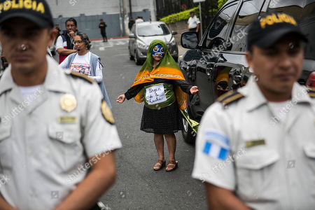 """A demonstrator wearing a costume that reads in Spanish: """"Virgin of the fight"""" protests outgoing President Jimmy Morales outside the Central American Parliament building where Morales will arrive to join the parliament as a lawmaker, in Guatemala City, . Guatemala will inaugurate on Tuesday a new president as Morales exits amid swirling corruption accusations"""