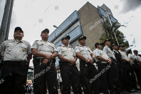 Police stand guard in front of the Central American Parliament, behind, where outgoing President Jimmy Morales will arrive to join the parliament as a lawmaker, in Guatemala City, . Guatemala will inaugurate on Tuesday a new president as Morales exits amid swirling corruption accusations