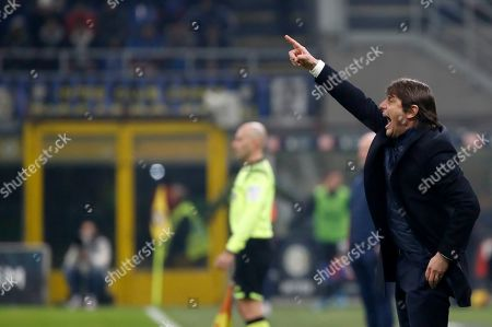 Inter Milan's head coach Antonio Conte gives instructions to his players during an Italian Cup soccer match between Inter Milan and Cagliari at the San Siro stadium, in Milan, Italy