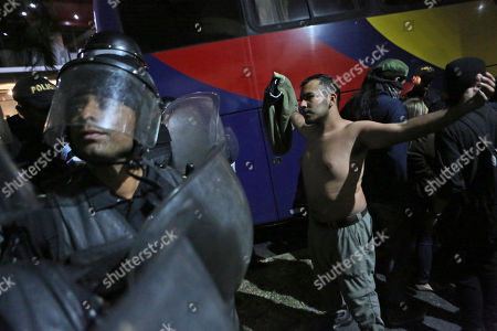 Protesters clash with anti-riot police as outgoing President Jimmy Morales enters the hotel where the Central American Parliament meets in Guatemala City late . Morales was sworn in as a deputy of the Central American parliament after being attacked by protesters at the hotel where they were then escorted by police