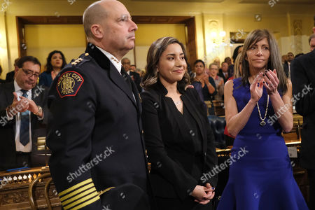 Laura Seals, the widow of Detective Joe Seals, center, and Jersey City Police Chief Michael Kelly, left, stand as the crowd applauds during New Jersey Gov. Phil Murphy's State of the State address in Trenton, N.J., . Murphy, a Democrat, delivered his second State of the State speech Tuesday before a joint session of the Democrat-led Legislature, sketching his agenda for the year