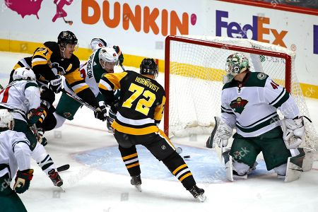 Pittsburgh Penguins' Evgeni Malkin (71) puts the puck behind Minnesota Wild goaltender Devan Dubnyk (40) with Jared Spurgeon (46) defending for a goal during the first period of an NHL hockey game in Pittsburgh