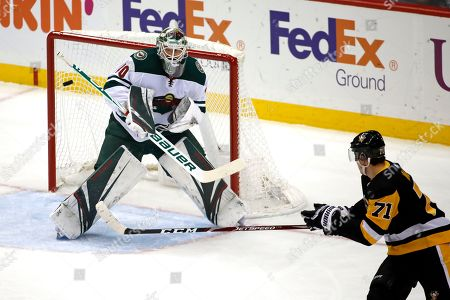 Minnesota Wild goaltender Devan Dubnyk (40) blocks a shot deflected by Pittsburgh Penguins' Evgeni Malkin (71) during the first period of an NHL hockey game in Pittsburgh