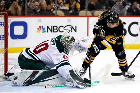 Minnesota Wild goaltender Devan Dubnyk (40) blocks a shot by Pittsburgh Penguins' Dominik Kahun (24) during the second period of an NHL hockey game in Pittsburgh