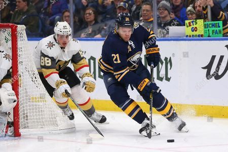 Buffalo Sabres forward Kyle Okposo (21) carries the puck past Vegas Golden Knights defenseman Nate Schmidt (88) during the first period of an NHL hockey game, in Buffalo, N.Y