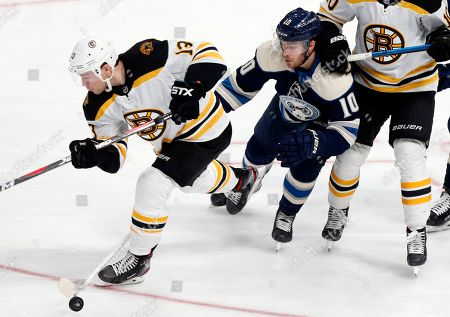 Columbus Blue Jackets forward Alexander Wennberg, middle, of Sweden, reaches for the puck against Boston Bruins forward Charlie Coyle during the third period an NHL hockey game in Columbus, Ohio, . The Blue Jackets won 3-0
