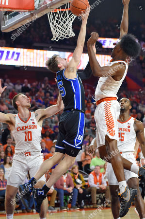 Duke's Alex O'Connell, center, drives to the basket works while defended by Clemson's Curran Scott, left, and John Newman lll during the first half of an NCAA college basketball game, in Clemson, S.C
