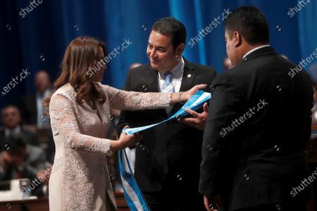 The former President of Guatemala Jimmy Morales (C), and his wife Patricia Marroquin (L), deliver the presidential band to the president of Congress Allan Rodriguez (R), during the inauguration ceremony for President of Guatemala Alejandro Giammattei (not pictured) at the National Theater in Guatemala City, Guatemala, 14 January 2020.