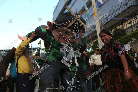 A woman hits a paper doll of outgoing President Jimmy Morales at the Central American Parliament headquarters in Guatemala City, . Protesters blocked Morales from entering a hotel where the Parliament was meeting and prevented him from being sworn in as a deputy