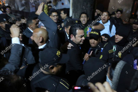 Outgoing President Jimmy Morales, center, is evacuated by police agents surrounded by protesters in Guatemala City, . Morales was trying to enter a hotel where the Central American Parliament meets, to be sworn in as a deputy