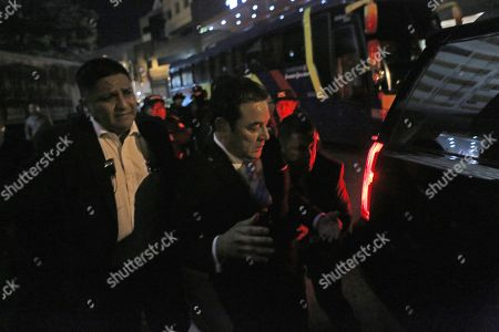 Protesters throw eggs at outgoing President Jimmy Morales as he is evacuated by police agents outside to a hotel in Guatemala City, . Morales was trying to enter a hotel where the Central American Parliament meets, to be sworn in as a deputy