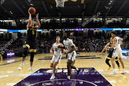 Iowa guard CJ Fredrick (5) shoots as Northwestern forward Jared Jones (4) stands nearby during the second half of an NCAA college basketball game, in Evanston, Ill