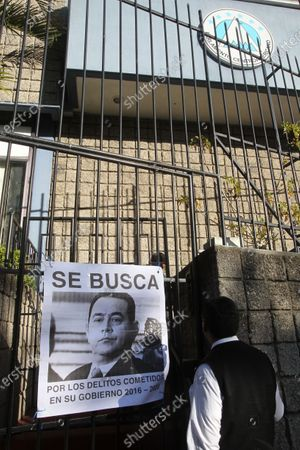 A man looks at a photo of outgoing Guatemalan President Jimmy Morales reading 'Wanted for Crimes committed during his mandate 2016-2020' during a protest in Guatemala City, Guatemala, 14 January 2020 (issued on 15 January 2020). Demonstrators were protesting against the swearing-in ceremony of Morales as MP at Parliament, a move that will allow him to keep exemption from prosecution for alleged charges of corruption and illegal election funding.