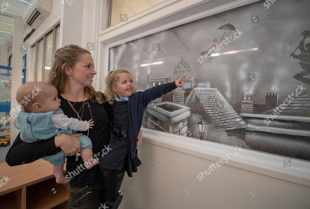 Editorial photo of Pictured Is Mother Jade Gingell 24 From Reading And Abigail 3 And Baby Jessica 6 Months. The Family Look At The Finished Window Art By Tom Baker An Artist Who Has A Seasonal Speciality Of Doing Window Art And Snowy Scenes Using Nothing But Spray Snow And A Scraper Blade. This Mary Poppins Themed Window Is In A Children's Clinic In The Royal Berkshire Hospital Reading.