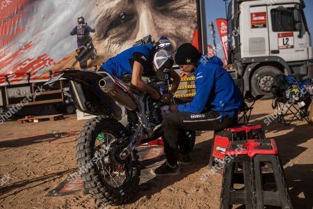 """Sara Garcia of Spain checks her Yamaha motorbike, next to his partner Javier Vega of Spain at the Dakar rally """"park ferme"""" in Wadi Al Dawasir, Saudi Arabia. Formerly known as the Paris-Dakar Rally, the race was created by Thierry Sabine after he got lost in the Libyan desert in 1977. Until 2008, the rallies raced across Africa, but threats in Mauritania led organizers to cancel that year's event and move it to South America. It has now shifted to Saudi Arabia. The race started on Jan. 5 with 560 drivers and co-drivers, some on motorbikes, others in cars or in trucks. Only 41 are taking part in the Original category"""
