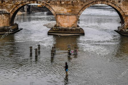Stock Image of A man is fishing in the cold water of the river Vardar in front of the old Stone Bridge in Skopje, Republic of North Macedonia, 15 January 2020.