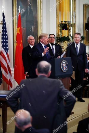 """President Donald Trump speaks about Sen. Chuck Grassley, R-Iowa, standing foreground, before signing """"phase one"""" of a US China trade agreement with Chinese Vice Premier Liu He, in the East Room of the White House, in Washington. With the President from left are Vice President Mike Pence, Treasury Secretary Stephen Mnuchin and U.S. Trade Representative Robert Lighthizer"""