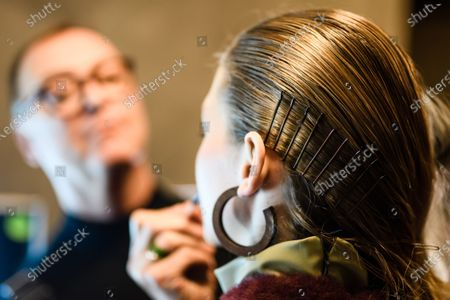 Stock Picture of A model with hair clips gets make-up applied during backstage preparations prior to the Dawid Tomaszewski show during the Berlin Fashion Week, in Berlin, Germany, 15 January 2020. The Fall/Winter 2020 collections are presented at the Berlin Fashion Week from 13 to 17 January.