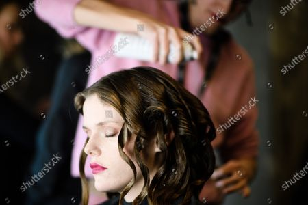 Stock Photo of A model receives hairspray during backstage preparations prior to the Dawid Tomaszewski show during the Berlin Fashion Week, in Berlin, Germany, 15 January 2020. The Fall/Winter 2020 collections are presented at the Berlin Fashion Week from 13 to 17 January.