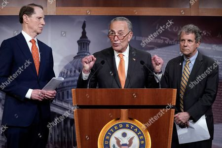 Senate Minority Leader Chuck Schumer, D-N.Y., Sen. Sherrod Brown, D-Ohio, right, and Senate Finance Committee ranking member Ron Wyden, D-Ore., discuss the U.S. China trade agreement during a news conference at the Capitol in Washington