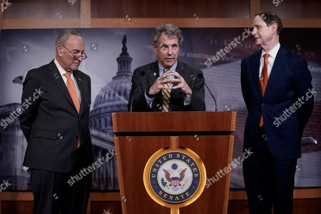 Senate Minority Leader Chuck Schumer, D-N.Y., left, listens as Sen. Sherrod Brown, D-Ohio, speaks along with Senate Finance Committee ranking member Ron Wyden, D-Ore., during a news conference about the U.S. China trade agreement at the Capitol in Washington