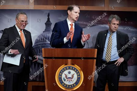 Stock Photo of Senate Minority Leader Chuck Schumer, D-N.Y., left, and Sen. Sherrod Brown, D-Ohio, right, listen as Senate Finance Committee ranking member Ron Wyden, D-Ore., speaks during a news conference at the Capitol about the U.S. China trade agreement in Washington