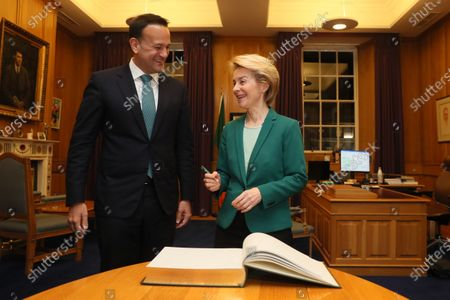 European Commission President Ursula von der Leyen (R) signing the visitors book as Taoiseach Leo Varadkar welcomes her to Government Buildings, Dublin, Ireland, 15 January 2020.