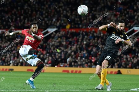 Manchester United's Fred, left, shoots on goal as Wolverhampton Wanderers' Joao Moutinho is seen on the right during the English FA Cup third round replay soccer match between Manchester United and Wolverhampton Wanderers at Old Trafford in Manchester, England