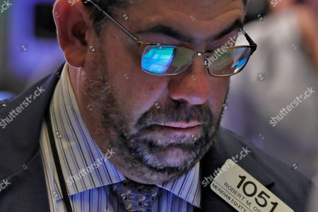 The handheld screen of trader Robert Oswald is reflected in his glasses as he works on the floor of the New York Stock Exchange, . Stocks are rising in afternoon trading Wednesday following the signing of a preliminary trade deal between the U.S. and China