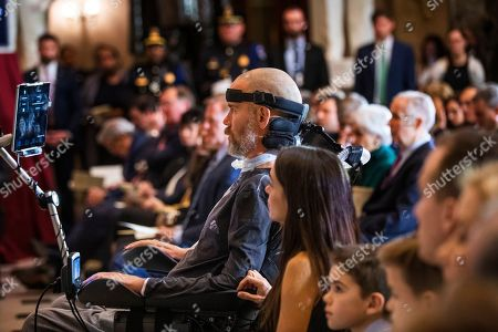 Steve Gleason, amyotrophic lateral sclerosis (ALS) advocate and former National Football League (NFL) player, listens to speeches during a Congressional Gold Medal ceremony honoring him in Statuary Hall at the Capitol Hill, in Washington