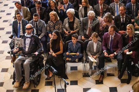 Steve Gleason, amyotrophic lateral sclerosis (ALS) advocate and former National Football League (NFL) player, left, and his former teammate New Orleans Saints quarterback Drew Brees, second from right, listen to speeches during a ceremony honoring Gleason with Congressional Gold Medal in Statuary Hall on Capitol Hill, in Washington