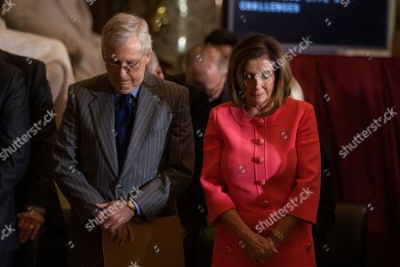 Stock Picture of Nancy Pelosi, Mitch McConnell. House Speaker Nancy Pelosi and Senate Majority Leader Mitch McConnell of Ky., bow their heads and pray during a Congressional Gold Medal ceremony honoring amyotrophic lateral sclerosis (ALS) advocate and former National Football League (NFL) player, Steve Gleason, in Statuary Hall on Capitol Hill, in Washington