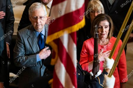 Stock Photo of Speaker of the House Nancy Pelosi (R) and Senate Majority Leader Mitch McConnell (L) attend a Congressional gold medal ceremony in honor of retired football player and advocate for patients with Lou Gehrig's disease Steve Gleason in Statuary Hall in the US Capitol in Washington, DC, 15 January 2020. Later in the day, Pelosi will send the articles of impeachment against President Trump to the Senate for a trial.