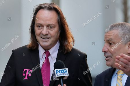T-Mobile chief executive John Legere speaks to reporters as he leaves the courthouse in New York, . Legere was in court to hear closing arguments in the case that could permit T-Mobile to merge with Sprint