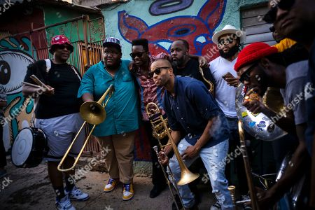 Trombonist Troy Andrews, center, and members of the The Soul Rebels Band from New Orleans pose with Cuban singer Cimafunk, third left, during the music conga through the streets of Old Havana during the activities of the 35th Havana Jazz Plaza festival in Havana, Cuba