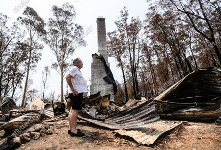 Peter Williams stands on the remains of his home, which was destroyed in the New Years Eve bushfire in Mogo, Australia, 15 January 2020 (issued 16 January 2020). Bushfires swept through Mogo on New Years Eve 2019 destroying several homes and businesses. Peter and Vanessa Williams lost both their home and their business which were adjacent to eachother in Mogo.