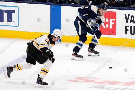 Columbus Blue Jackets forward Alexander Wennberg, right, of Sweden, passes in front of Boston Bruins forward Chris Wagner during an NHL hockey game in Columbus, Ohio, . The Blue Jackets won 3-0