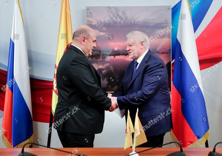 In this photo provided by The State Duma, The Federal Assembly of The Russian Federation, Just Russia party leader Sergei Mironov, right, shakes hands with Russian Tax Service chief Mikhail Mishustin who was nominated to replace Medvedev, during their meeting in the State Duma, the Lower House of the Russian Parliament in Moscow, Russia, . Russian President Vladimir Putin has named Tax Service chief Mikhail Mishustin as Russia's new prime minister