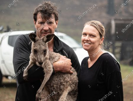 Gary Henderson (L) holds a young injured kangaroo which he and his partner Sara Tilling (R) are nursing back to health in Cobargo, Australia, 16 January 2020. Henderson and Tilling used to run the Cobargo Wildlife Sanctuary from their home, which was lost in a bushfire along with all their animals, and have only been able to rescue one kangaroo. Bushfires swept through Cobargo on New Year's Eve 2019 killing two and destroying several homes and businesses.