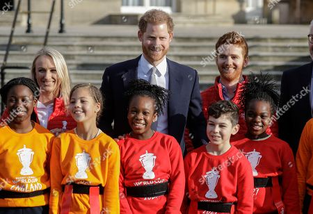 Prince Harry poses with schoolchildren and Rugby League World Cup 2021 ambassadors James Simpson, right, and Jody Cunningham in the gardens at Buckingham Palace in London,. Prince Harry, will host the Rugby League World Cup 2021 draw at Buckingham Palace, prior to the draw, The Duke met with representatives from all 21 nations taking part in the tournament, as well as watching children from a local school play rugby league in the Buckingham Palace gardens