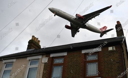 A Virgin Atlantic passenger aircraft flies over a residential area as it prepares to land at Heathrow Airport in London, Britain, 16 January 2020. The owner of British Airways (BA), International Airlines Group (IAG), on 15 January filed a complaint to the EU over the British Government's 120-million-euro bail-out plan for the UK regional airline Flybe. Willie Walsh, Chief Executive of IAG, said the bail-out would be a 'blatant misuse of public funds'.