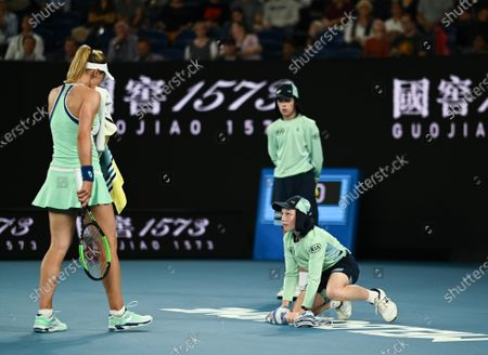 A ballboy wiping the court as Lesia Tsurenko watches on during her Women's Singles First Round match