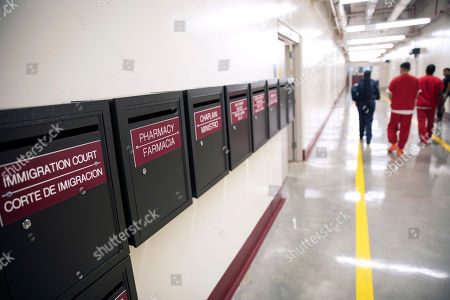 Mail boxes for various departments line a hallway as detainees walk through the Stewart Detention Center, in Lumpkin, Ga. The rural town is about 140 miles southwest of Atlanta and next to the Georgia-Alabama state line. The town's 1,172 residents are outnumbered by the roughly 1,650 male detainees that U.S. Immigration and Customs Enforcement said were being held in the detention center in late November