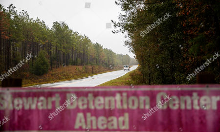 A detainee transport van travels the rural road back to the Stewart Detention Center in Lumpkin, Ga. The rural town is about 140 miles southwest of Atlanta and next to the Georgia-Alabama state line. The town's 1,172 residents are outnumbered by the roughly 1,650 male detainees that U.S. Immigration and Customs Enforcement said were being held in the detention center in late November