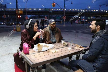 """Amani Al-Khatahtbeh, founder of MuslimGirl.com, left, sips a soda while talking with old friends Mohammed Ali, right, and Saad Khan outside of a corner market in the Brooklyn borough of New York. Al-Khatahtbeh stays in New Jersey with her family when in town on business. Her home and office are in Los Angeles. Growing up, she remembers not having many friends and was often bullied. """"High school kind of like made me into the person that I needed to be to create MuslimGirl,"""" she says"""